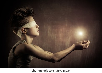 Conceptual Glowing Light Over the Open Bare Hands of a Blind Boy with Eyes Covered with Bandage Against Abstract Gray Background.