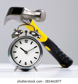 Conceptual Hammer Tool on a Round Alarm Clock in Close up, Against Gray Wall Background