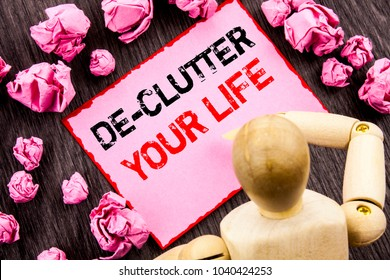 Conceptual hand text showing De-Clutter Your Life. Concept meaning Free Less Chaos Fresh Clean Routine written Sticky Note Holding By Sculpture the wooden background.