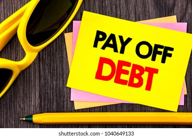 Conceptual hand text showing Pay Off Debt. Business photo showcasing Reminder To Paying Owed Financial Credit Loan Bills written Stiky Note Paper with Pen the wood background.
