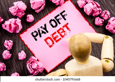 Conceptual hand text showing Pay Off Debt. Concept meaning Reminder To Paying Owed Financial Credit Loan Bills written Sticky Note Holding By Sculpture the wooden background.