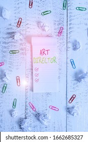 Conceptual hand writing showing Art Director. Business photo showcasing responsible for overseeing the artistic aspects of a film Stripped ruled notepad clips paper balls wooden background.