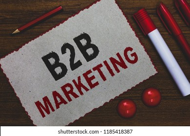 Conceptual hand writing showing B2B Marketing. Business photo showcasing Partnership Companies Supply Chain Merger Leads Resell White paper red borders markers pencils wooden background.