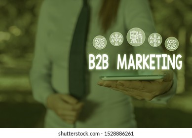 Conceptual hand writing showing B2B Marketing. Business photo showcasing Partnership Companies Supply Chain Merger Leads Resell Woman wear work suit presenting presentation smart device.