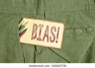 Conceptual hand writing showing Bias. Business photo showcasing inclination or prejudice for or against one demonstrating group Writing equipment and yellow notepaper in pocket of trousers.