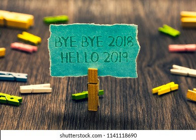 Conceptual hand writing showing Bye Bye 2018 Hello 2019. Business photo showcasing Starting new year Motivational message 2018 is over Paperclip retain blue cardboard blurry woody desk paper clip.