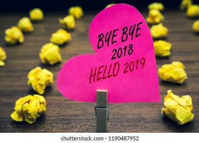 Conceptual hand writing showing Bye Bye 2018 Hello 2019. Business photo text Starting new year Motivational message 2018 is over Paperclip hold pink written heart woody floor with yellow lobs.
