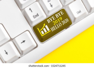 Conceptual hand writing showing Bye Bye 2019 Hello 2020. Business photo text Starting new year Motivational message 2019 is over White pc keyboard with note paper above the white background.