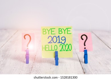 Conceptual hand writing showing Bye Bye 2019 Hello 2020. Business photo text Starting new year Motivational message 2019 is over Crumbling sheet with paper clips placed on the wooden table.