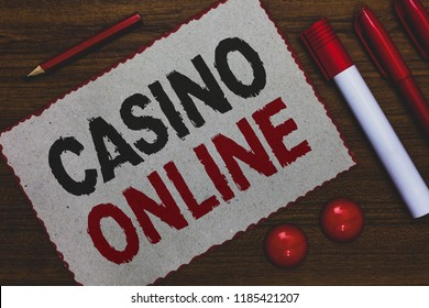 Conceptual hand writing showing Casino Online. Business photo showcasing Computer Poker Game Gamble Royal Bet Lotto High Stakes White paper red borders markers pencils wooden background.