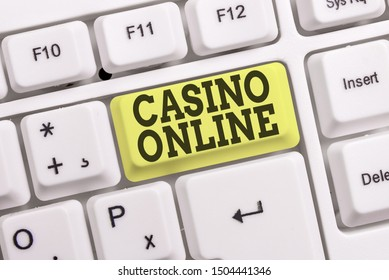 Conceptual hand writing showing Casino Online. Business photo text Computer Poker Game Gamble Royal Bet Lotto High Stakes White pc keyboard with note paper above the white background.