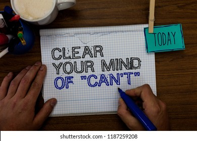 Conceptual hand writing showing Clear Your Mind Of Can t not. Business photo showcasing Have a positive attitude thinking motivation Hand hold pen paper clip written notepad pen case coffee mug.