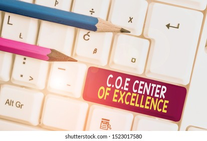 Conceptual hand writing showing Coe Center Of Excellence. Business photo text being alpha leader in your position Achieve White pc keyboard with note paper above the white background.