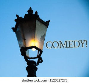 Conceptual hand writing showing Comedy Call. Business photo text Fun Humor Satire Sitcom Hilarity Joking Entertainment Laughing Light post blue sky enlighten ideas old vintage antique Victorian.