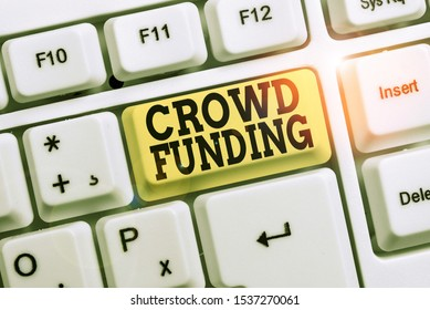 Conceptual hand writing showing Crowd Funding. Business photo text Fundraising Kickstarter Startup Pledge Platform Donations White pc keyboard with note paper above the white background.