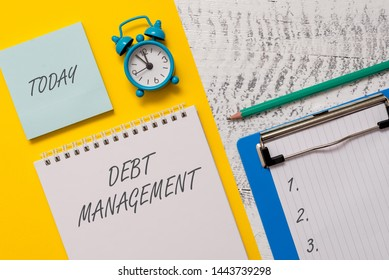 Conceptual hand writing showing Debt Management. Business photo showcasing The formal agreement between a debtor and a creditor Spiral notepad sheet marker alarm clock wooden background.