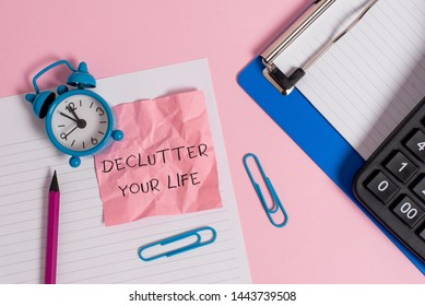 Conceptual hand writing showing Declutter Your Life. Business photo text To eliminate extraneous things or information in life Paper sheet clipboard pencil calculator clock colored background.
