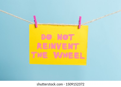 Conceptual hand writing showing Do Not Reinvent The Wheel. Business photo text stop duplicating a basic method previously done Clothespin rectangle shaped paper reminder white wood desk.