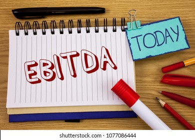 Conceptual hand writing showing Ebitda. Business photo text Earnings before tax is measured to evaluate company performance written on Noteoad on wooden background Today Pen Pencil next to it
