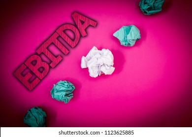 Conceptual hand writing showing Ebitda. Business photo text Earnings Before Interest Taxes Depreciation Amortization Abbreviation Ideas messages pink background crumpled papers several tries.