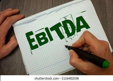 Conceptual hand writing showing Ebitda. Business photo text Earnings Before Interest Taxes Depreciation Amortization Abbreviation Man hold holding black marker gruge notebook wooden wood table.