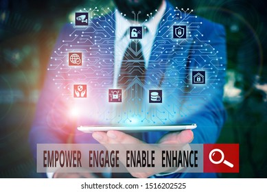 Conceptual hand writing showing Empower Engage Enable Enhance. Business photo text Empowerment Leadership Motivation Engagement Male wear formal work suit presenting presentation smart device.