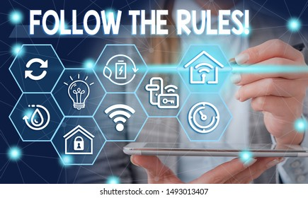 Conceptual hand writing showing Follow The Rules. Business photo showcasing go with regulations governing conduct or procedure Female human wear formal work suit presenting smart device.