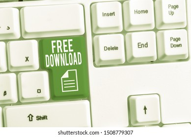 Conceptual hand writing showing Free Download. Business photo showcasing Key in Transfigure Initialize Freebies Wireless Images White pc keyboard with note paper above the white background.