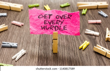 Conceptual hand writing showing Get Over Every Hurdle. Business photo showcasing Overcome any obstacle problem trouble adversities Paperclip hold pink note with texts many clips wooden floor.