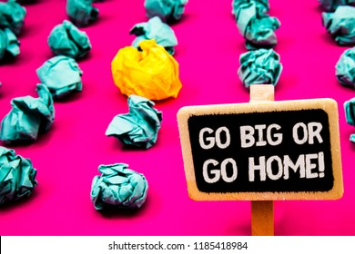 Conceptual hand writing showing Go Big Or Go Home Motivational Call. Business photo text Mindset Ambitious Impulse Persistence Blackboard with white letter pink base much green paper lobs.