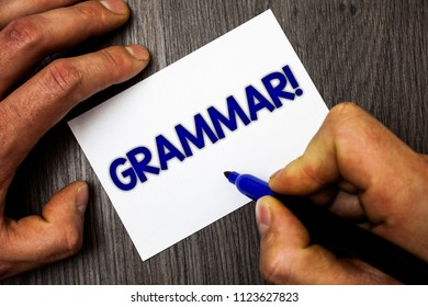 Conceptual hand writing showing Grammar Motivational Call. Business photo showcasing System and Structure of a Language Writing Rules Man working holding blue marker ideas paper wooden table.