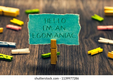 Conceptual hand writing showing Hello I am An Egomaniac. Business photo showcasing Selfish Egocentric Narcissist Self-centered Ego Paperclip retain blue cardboard blurry woody desk paper clip.