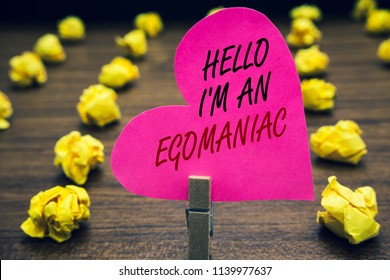 Conceptual hand writing showing Hello I am An Egomaniac. Business photo text Selfish Egocentric Narcissist Self-centered Ego Paperclip hold pink written heart woody floor with yellow lobs.