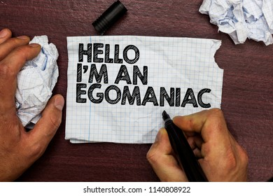 Conceptual hand writing showing Hello I am An Egomaniac. Business photo text Selfish Egocentric Narcissist Self-centered Ego Hand hold pen sketch word on torn page woody deck hand paper ball.