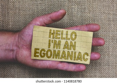 Conceptual hand writing showing Hello I am An Egomaniac. Business photo showcasing Selfish Egocentric Narcissist Self-centered Ego Thick gray paper with words human hands jute sack background.