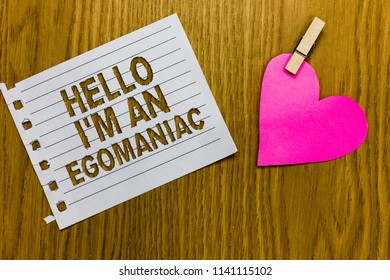 Conceptual hand writing showing Hello I am An Egomaniac. Business photo showcasing Selfish Egocentric Narcissist Self-centered Ego Yellow woody deck word with white page paper clip grip heart.