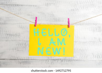 Conceptual hand writing showing Hello I Am New. Business photo text used as greeting or to begin telephone conversation Clothespin rectangle shaped paper reminder white wood desk.