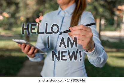 Conceptual hand writing showing Hello I Am New. Business photo text used as greeting or to begin telephone conversation Woman in a blue shirt pointing with her finger into empty space.