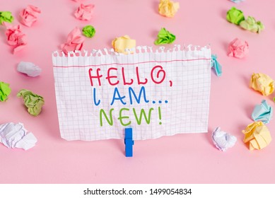 Conceptual hand writing showing Hello I Am New. Business photo showcasing used greeting or begin telephone conversation Colored crumpled papers empty reminder pink floor clothespin.