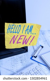 Conceptual hand writing showing Hello I Am New. Business photo showcasing used as greeting or to begin telephone conversation Note paper taped to black screen near keyboard stationary.