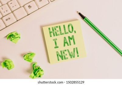 Conceptual hand writing showing Hello I Am New. Business photo text used as greeting or to begin telephone conversation Green note paper with pencil on white background and pc keyboard.