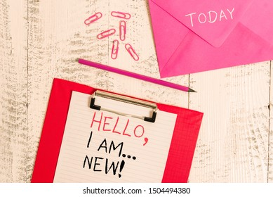 Conceptual hand writing showing Hello I Am New. Business photo showcasing used greeting or begin telephone conversation Colored clipboard paper sheet pencil clips wooden background.