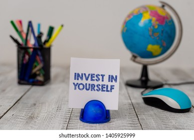Conceptual hand writing showing Invest In Yourself. Business photo showcasing learn new things or materials thus making your lot better Stationary and computer mouse with globe on the wooden desk.