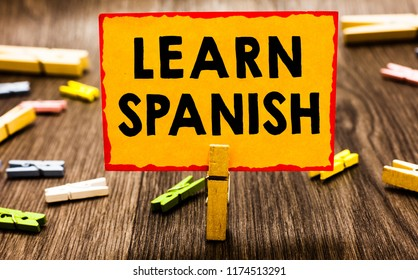 Conceptual hand writing showing Learn Spanish. Business photo showcasing Translation Language in Spain Vocabulary Dialect Speech Clothespin holding orange paper note clothespin wooden floor.