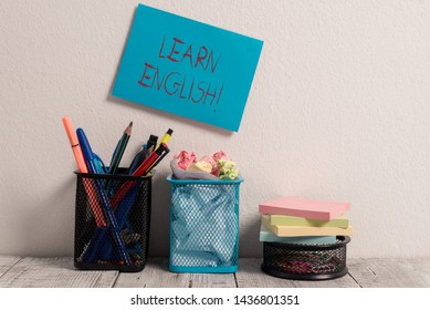 Conceptual hand writing showing Learn English. Business photo text gain acquire knowledge in new language by study Blue Sticky Card on Wall Two Pencil Pots Mesh Paperclip Notes.