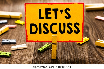 Conceptual hand writing showing Let s is Discuss. Business photo showcasing Permit to Talk Open Up Go Over a Topic Chat Sharing Clothespin holding orange paper note clothespin wooden floor.