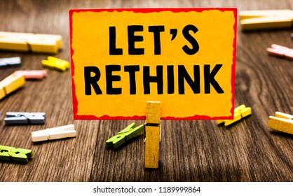 Conceptual hand writing showing Let s is Rethink. Business photo showcasing an Afterthought To Remember Reconsider Reevaluate Clothespin holding orange paper note clothespin wooden floor.