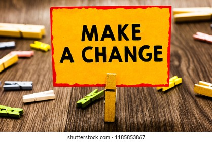 Conceptual hand writing showing Make A Change. Business photo showcasing Create a Difference Alteration Have an Effect Metamorphose Clothespin holding orange paper note clothespin wooden floor.