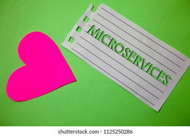 Conceptual hand writing showing Microservices. Business photo showcasing Software development technique Decomposing an application Small paper drawing heart green background remember message.