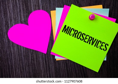 Conceptual hand writing showing Microservices. Business photo text Software development technique Decomposing an application Pinned multi colour cards heart polish dark lining background.